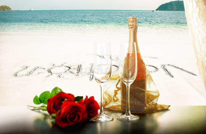Vacaciones de la tarjeta del día de San Valentín con la botella y los vidrios del champán con la flor color de rosa en la playa fotos de archivo