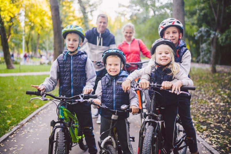 Vacaciones de los deportes de la familia del tema en parque en naturaleza familia caucásica amistosa grande de seis bicis de mont fotos de archivo libres de regalías