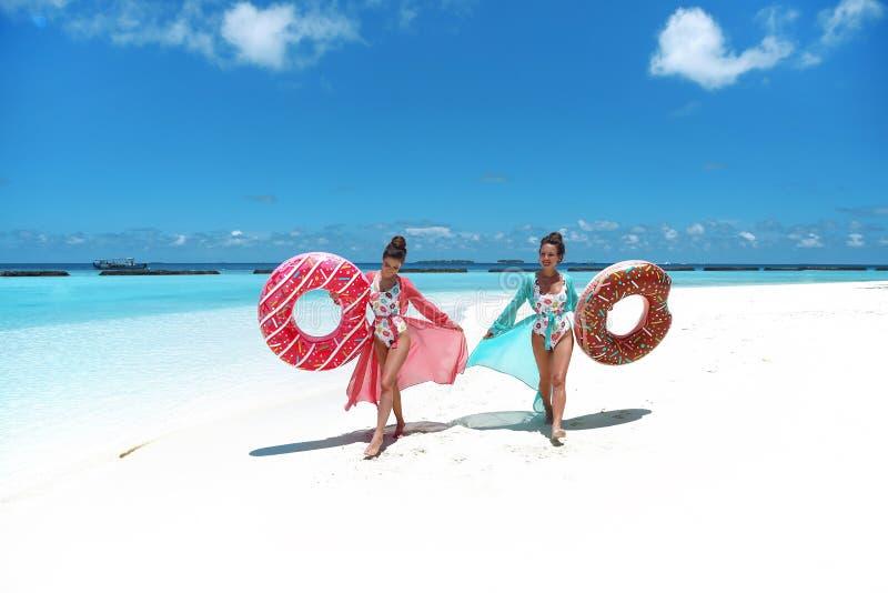 Vacaciones de verano Dos mujeres libres felices con el colchón inflable del flotador del buñuelo Muchachas que llevan el goce del imágenes de archivo libres de regalías