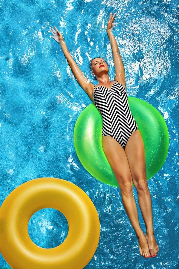Vacaciones de verano El tomar el sol de la mujer, flotando en agua de la piscina fotos de archivo