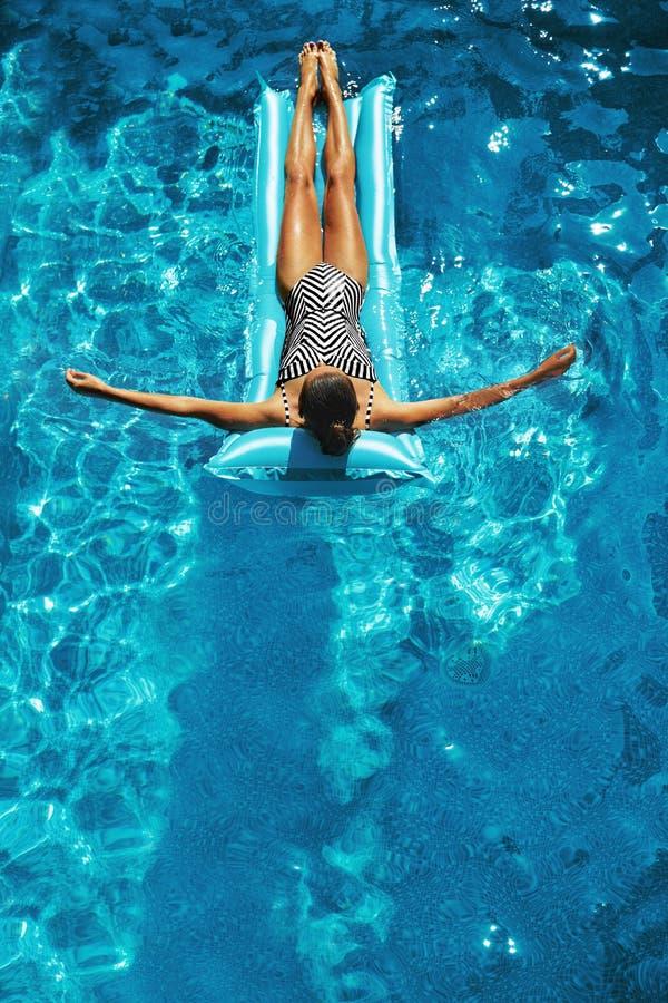 Vacaciones de verano El tomar el sol de la mujer, flotando en agua de la piscina imagen de archivo libre de regalías
