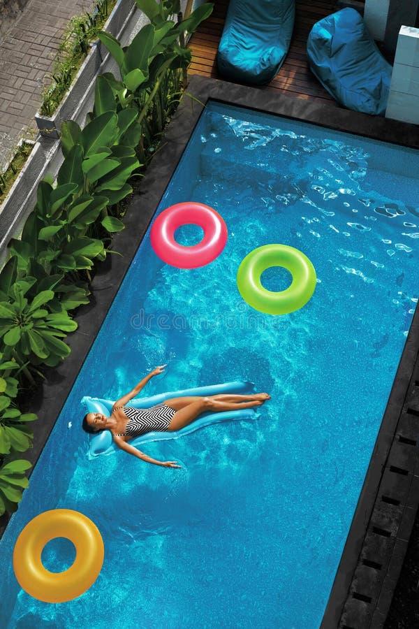 Vacaciones de verano El tomar el sol de la mujer, flotando en agua de la piscina imágenes de archivo libres de regalías