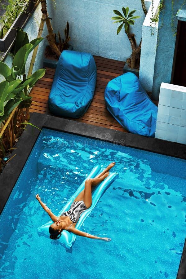 Vacaciones de verano El tomar el sol de la mujer, flotando en agua de la piscina imagenes de archivo