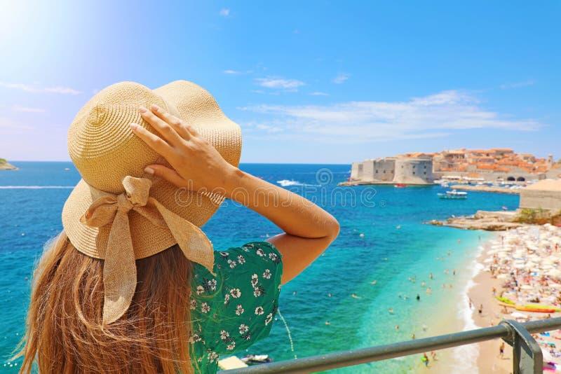 Vacaciones de verano en Croacia Opinión trasera la mujer joven que sostiene sombrero con la ciudad en el fondo, Croacia, Europa d imagen de archivo libre de regalías