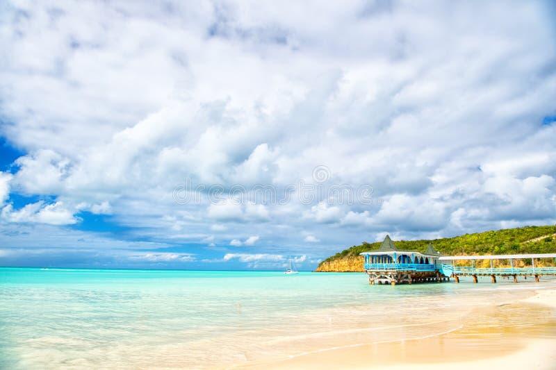 Vacaciones de verano en el Caribe Playa del mar con el refugio de madera en Antigua Embarcadero en agua de la turquesa en fondo d imagen de archivo