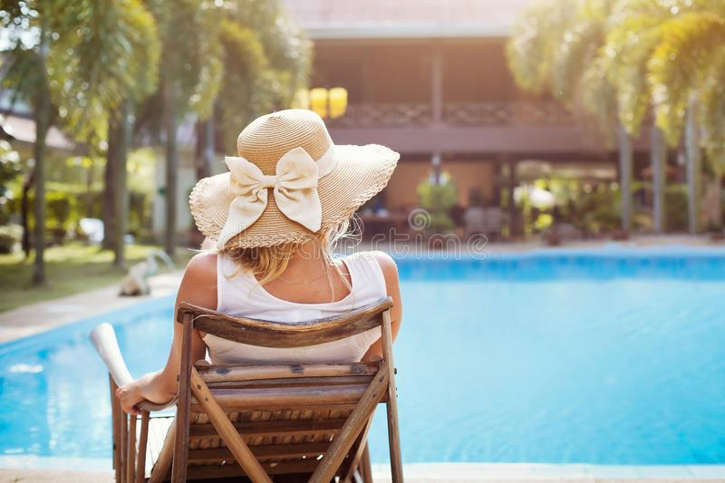 Vacaciones de verano en el hotel de lujo, mujer que se relaja en deckchair fotografía de archivo