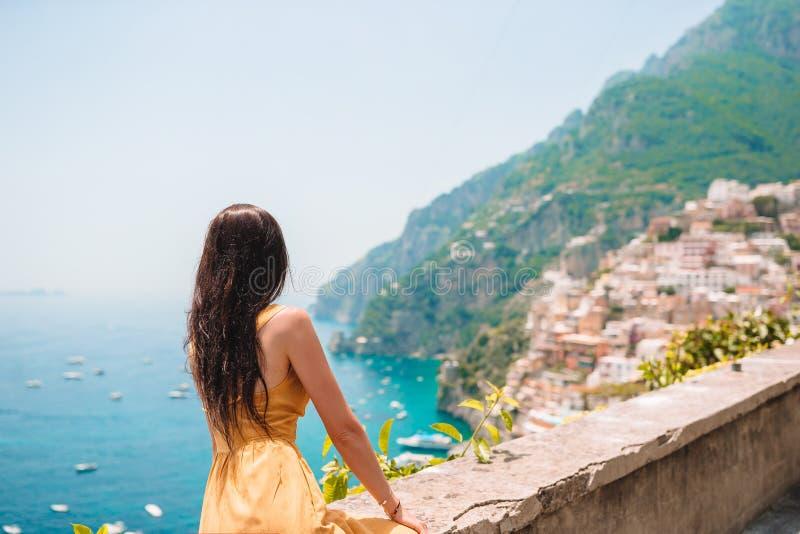 Vacaciones de verano en Italia Mujer joven en el pueblo en el fondo, costa de Amalfi, Italia de Positano foto de archivo libre de regalías