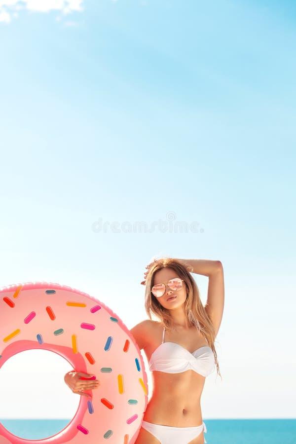 Vacaciones de verano Goce de la mujer del bronceado en el bikini blanco con el colchón del buñuelo cerca de la piscina imágenes de archivo libres de regalías