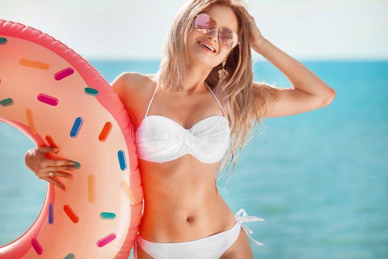 Vacaciones de verano Goce de la mujer del bronceado en el bikini blanco con el colchón del buñuelo cerca del océano fotos de archivo libres de regalías