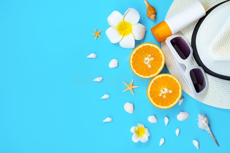 Vacaciones de verano hermosas, accesorios de la playa, gafas de sol, sombrero, naranja, sunblock y c?scaras en fondos azules fotos de archivo libres de regalías