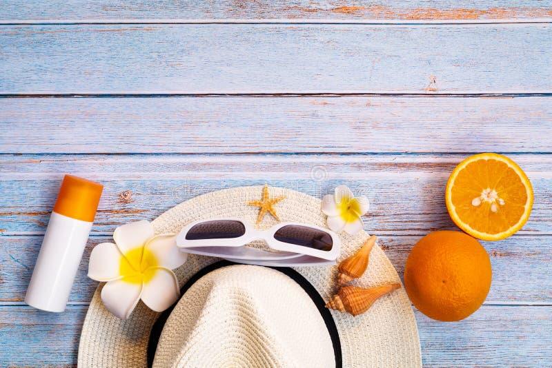 Vacaciones de verano hermosas, accesorios de la playa, gafas de sol, sombrero, sunblock y naranja en fondos de madera foto de archivo