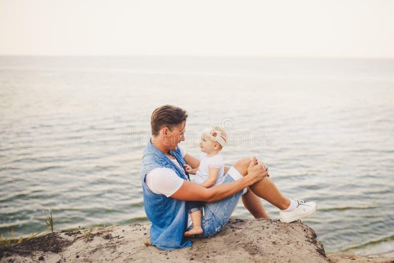 Vacaciones de verano de la familia en naturaleza el padre y la pequeña hija se sientan en el acantilado arenoso por un año con la imágenes de archivo libres de regalías