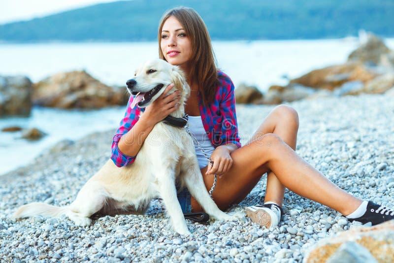 Vacaciones de verano, mujer con un perro en un paseo en la playa imagenes de archivo