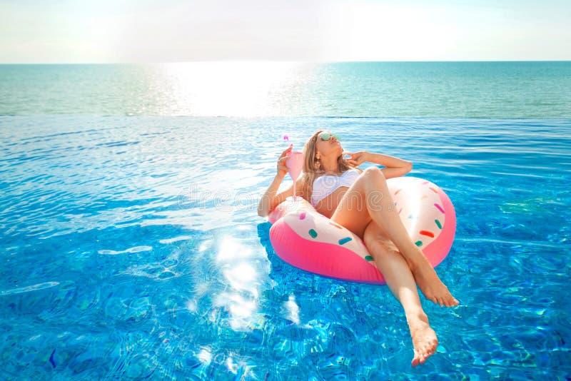 Vacaciones de verano Mujer en bikini en el colchón inflable del buñuelo en la piscina del BALNEARIO foto de archivo libre de regalías