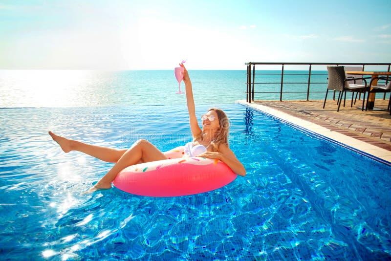 Vacaciones de verano Mujer en bikini en el colchón inflable del buñuelo en la piscina del BALNEARIO fotografía de archivo