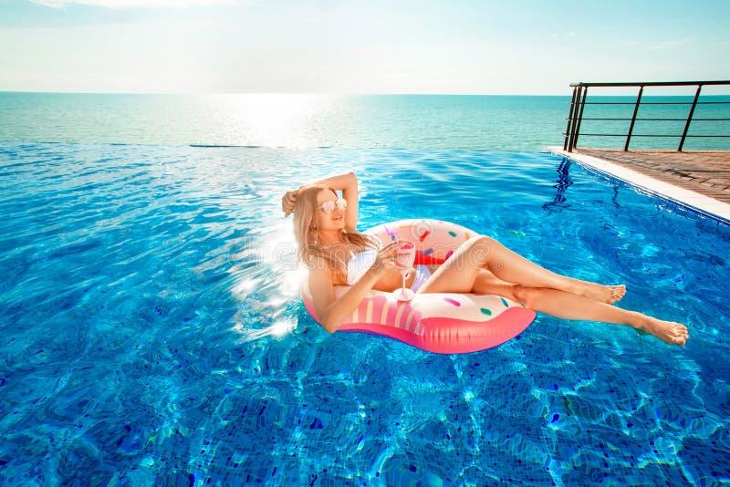Vacaciones de verano Mujer en bikini en el colchón inflable del buñuelo en la piscina del BALNEARIO fotos de archivo