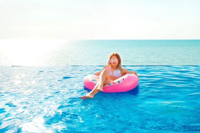 Vacaciones de verano Mujer en bikini en el colchón inflable del buñuelo en la piscina del BALNEARIO foto de archivo