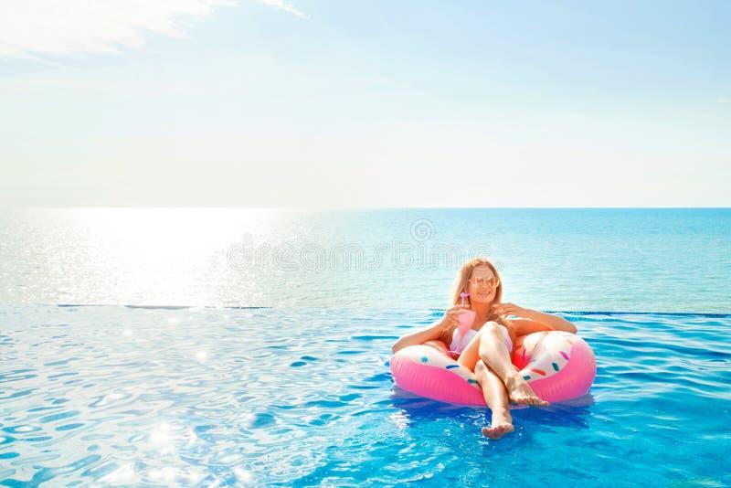Vacaciones de verano Mujer en bikini en el colchón inflable del buñuelo en la piscina del BALNEARIO imagen de archivo libre de regalías