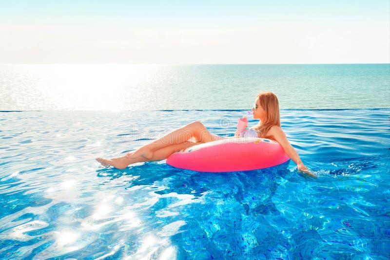 Vacaciones de verano Mujer en bikini en el colchón inflable del buñuelo en la piscina del BALNEARIO imagenes de archivo