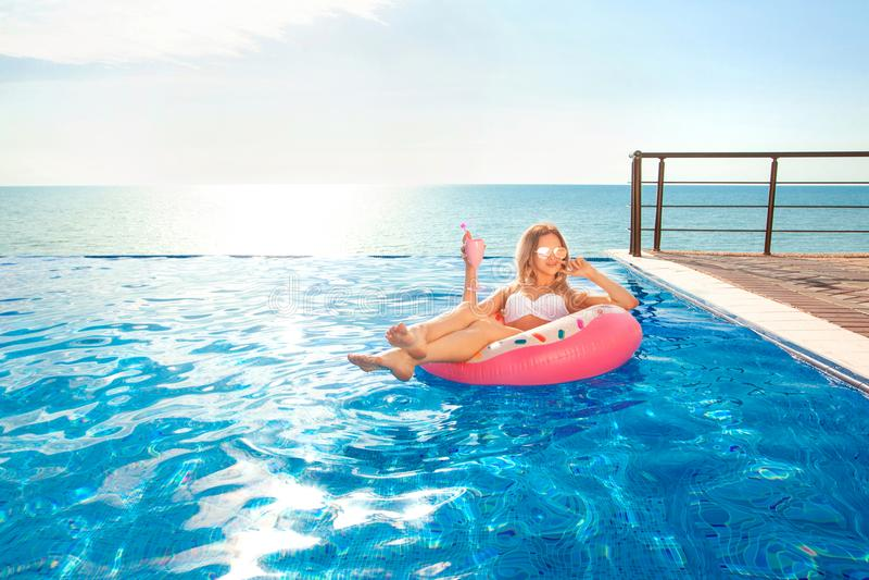 Vacaciones de verano Mujer en bikini en el colchón inflable del buñuelo en la piscina del BALNEARIO fotografía de archivo libre de regalías