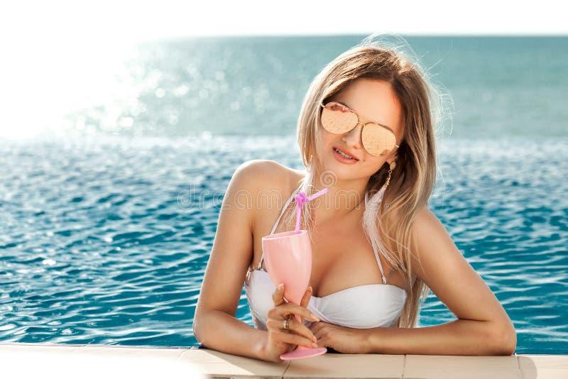 Vacaciones de verano Mujer en bikini en el colchón inflable del buñuelo en la piscina del BALNEARIO con el coctail foto de archivo libre de regalías
