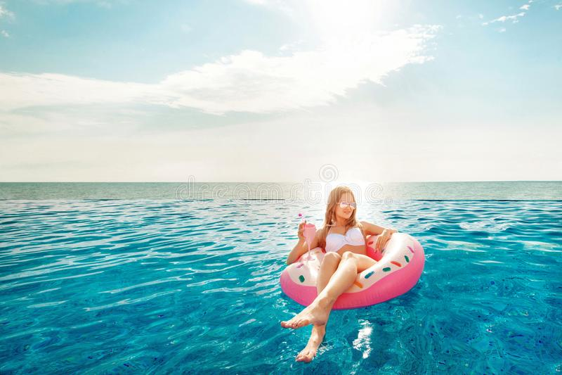 Vacaciones de verano Mujer en bikini en el colchón inflable del buñuelo en la piscina del BALNEARIO Playa en el mar azul imagen de archivo