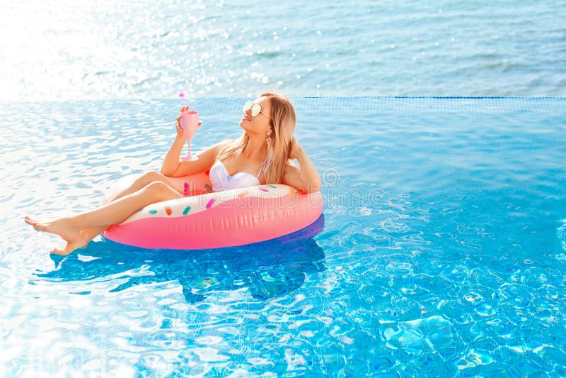Vacaciones de verano Mujer en bikini en el colchón inflable del buñuelo en la piscina del BALNEARIO Playa en el mar azul fotografía de archivo