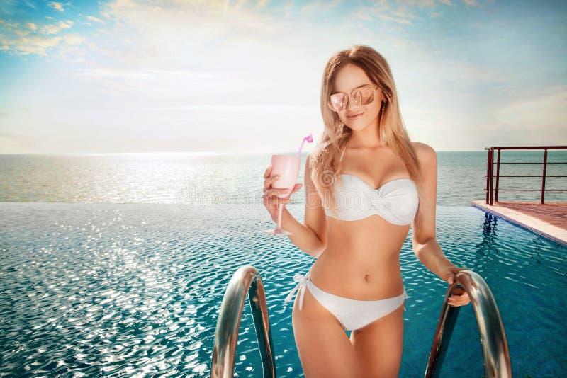 Vacaciones de verano Mujer en bikini en el colchón inflable en la piscina del BALNEARIO con el coctail fotos de archivo libres de regalías