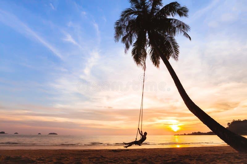 Vacaciones de verano, mujer feliz en el oscilación en la playa tropical, vacaciones fotos de archivo