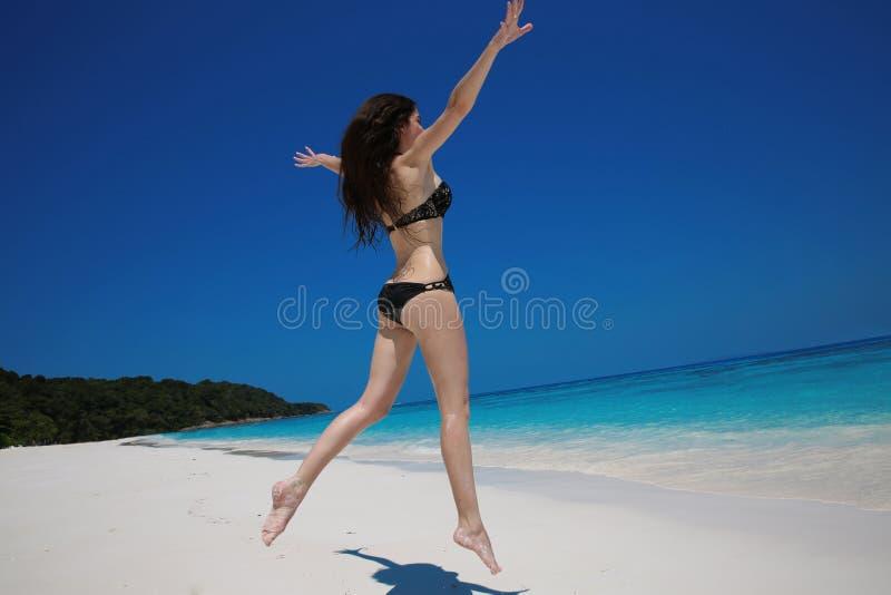 Vacaciones de verano Mujer feliz que corre y que salta en la playa exótica foto de archivo