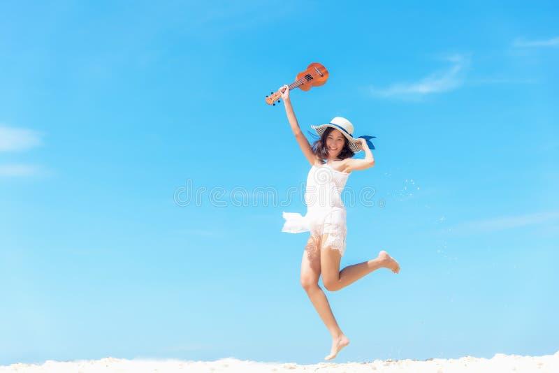 Vacaciones de verano Mujeres asiáticas que huelen que se relajan y que saltan con el ukelele en la playa, así que felices y de lu fotos de archivo