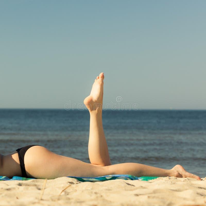 Vacaciones de verano. Piernas de tomar el sol a la muchacha en la playa imágenes de archivo libres de regalías