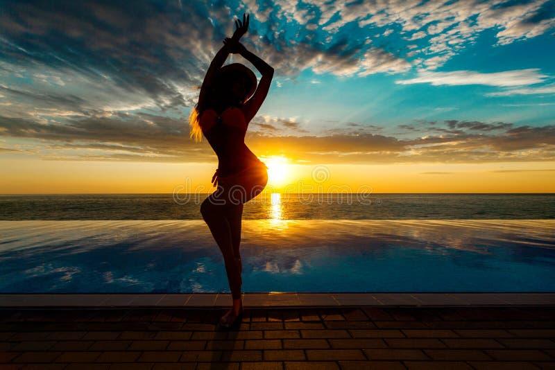 Vacaciones de verano Silueta de la mujer del baile de la belleza en puesta del sol cerca de la piscina con vista al mar fotos de archivo libres de regalías