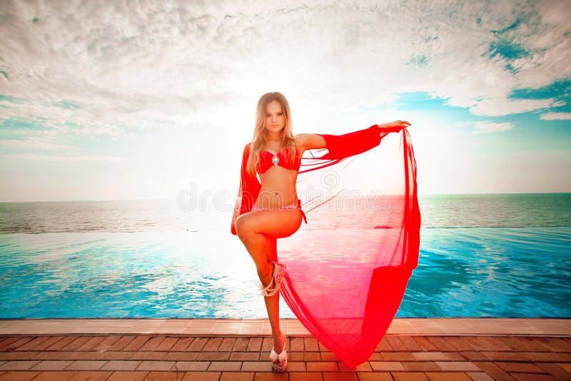 Vacaciones de verano Silueta de la mujer del baile de la belleza en puesta del sol cerca de la piscina con vista al mar imagen de archivo libre de regalías