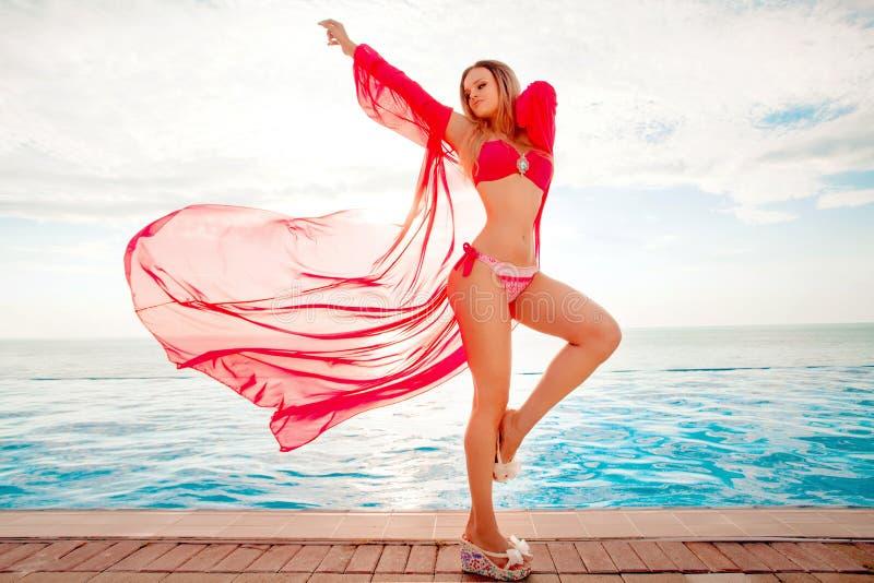 Vacaciones de verano Silueta de la mujer del baile de la belleza en puesta del sol cerca de la piscina con vista al mar imagenes de archivo