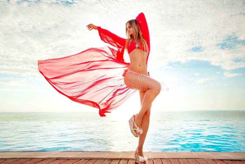 Vacaciones de verano Silueta de la mujer del baile de la belleza en puesta del sol cerca de la piscina con vista al mar Playa en  imagenes de archivo