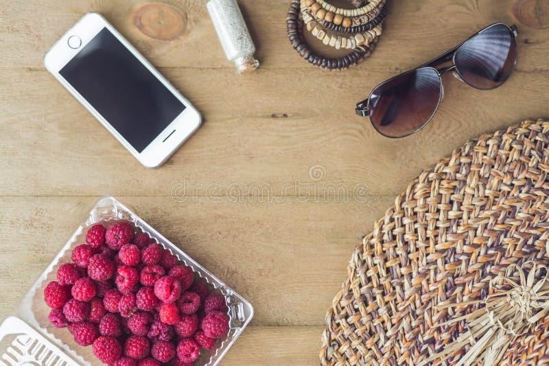 Vacaciones de verano, vacaciones, concepto de la relajación Las frambuesas, sombrero de paja, smartphone, gafas de sol desde arri fotos de archivo libres de regalías