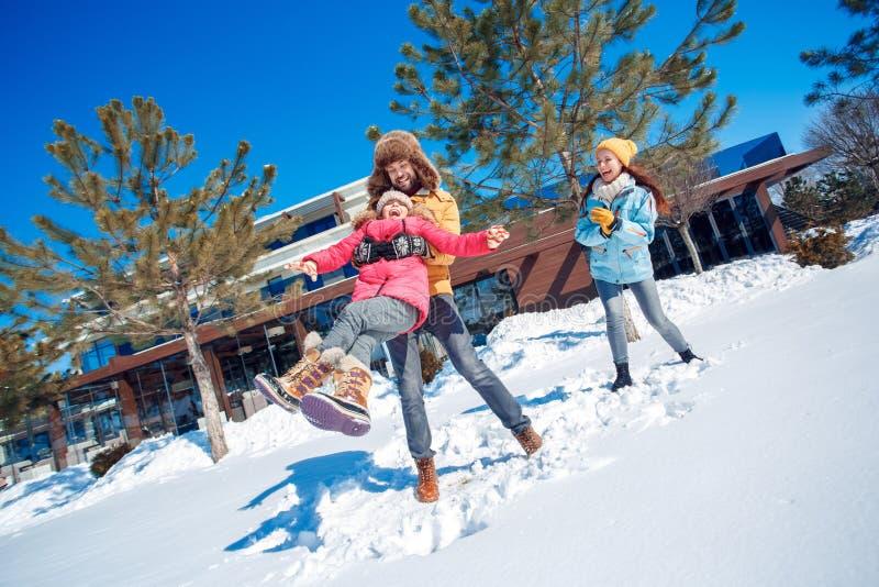 Vacaciones del invierno Hombre del tiempo de la familia junto al aire libre que lleva a cabo la risa de giro de la muchacha emoci fotografía de archivo
