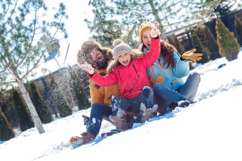 Vacaciones del invierno Tiempo de la familia junta al aire libre que sienta la risa de la nieve que lanza alegre imágenes de archivo libres de regalías