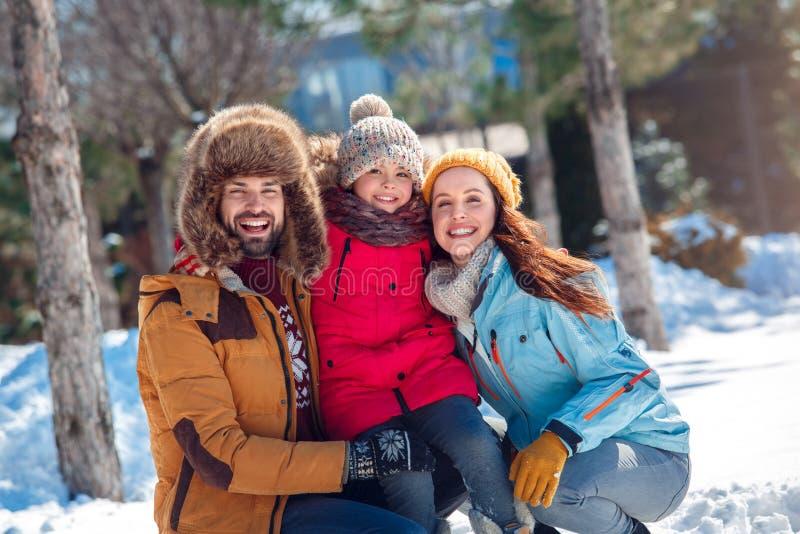 Vacaciones del invierno Tiempo de la familia junto al aire libre que se sienta abrazando la sonrisa feliz fotografía de archivo libre de regalías