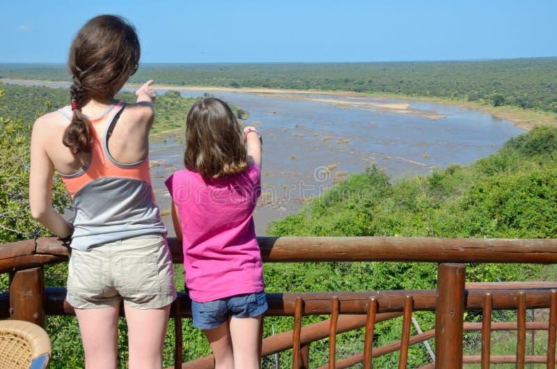 Vacaciones del safari de la familia en Suráfrica, la madre y la hija mirando la opinión africana hermosa del río, parque de Kruge fotos de archivo