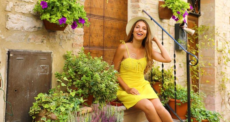 Vacaciones en Italia. Joven feliz sentada en un escalón entre coloridas flores y plantas en el pequeño medieval de Asís imagenes de archivo