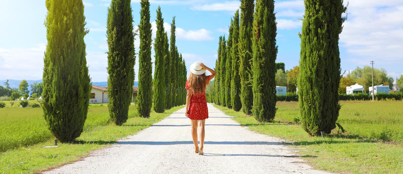 Vacaciones en Toscana. Panorámica de la bandera vista de una joven hermosa mujer caminando en una calle típica de la Toscana. Pa fotografía de archivo libre de regalías