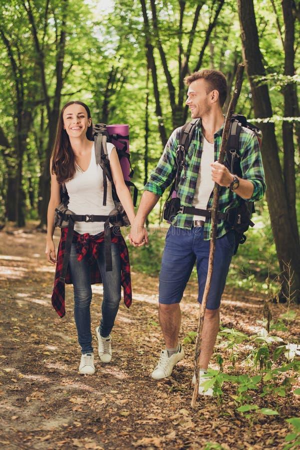 Vacaciones junto Pares jovenes felices que caminan en el bosque, manos de las tenencias, sonrisa, presentando para un retrato de  foto de archivo