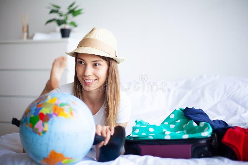 Vacaciones La mujer que se está preparando para la muchacha hermosa joven del resto se sienta en la cama Retrato de una mujer son fotografía de archivo