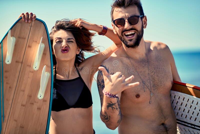 Vacaciones Pares extremos del deporte de las personas que practica surf que caminan en la playa imagen de archivo
