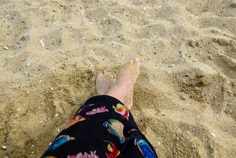 Vacaciones, piernas delgadas del resto de danza de la mujer en la arena imagen de archivo