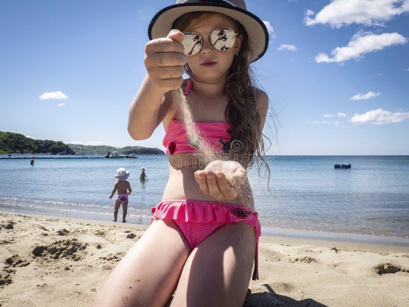 Vacaciones por el mar: una niña en gafas de sol y un sombrero vierte sus manos en la arena en una playa del mar cerca del agua fotos de archivo libres de regalías