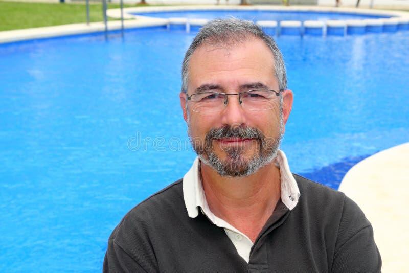 Vacaciones sonrientes mayores del hombre en la piscina azul feliz foto de archivo