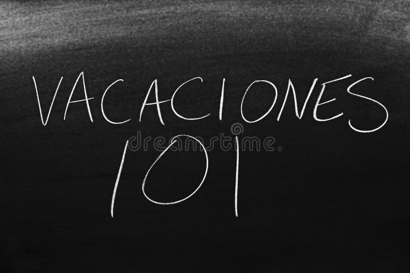 Vacaciones 101 sur un tableau noir Traduction : Vacances 101 photo libre de droits